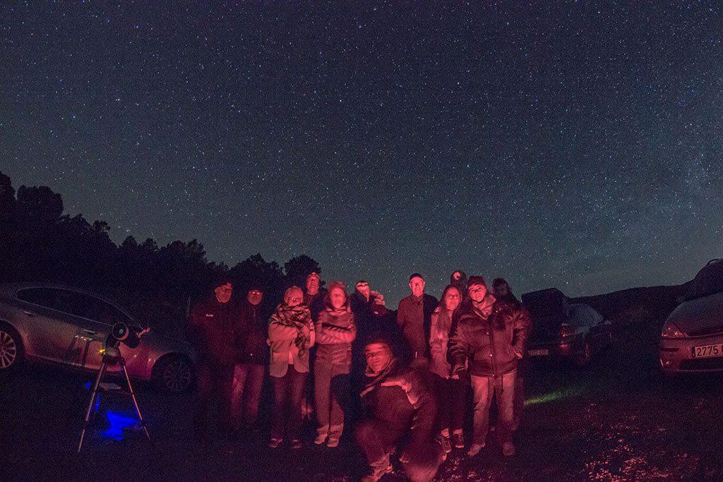 Grupo de personas durante una observación astronómica. Aparece un grupo de hombres y mujeres muy abrigados, bajo un cielo estrellado. Hay también algún telescopio. Están iluminados solo por la tenue luz de una linterna. Disfrutan del cielo estrellado.