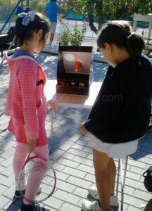 Dos niñas observan un eclipse solar en un SolarScope. A pesar de ser un instrumento seguro muchos niños tienen el impulso de meter la cabeza dentro para ver de dónde sale la luz, lo que supone un peligro.